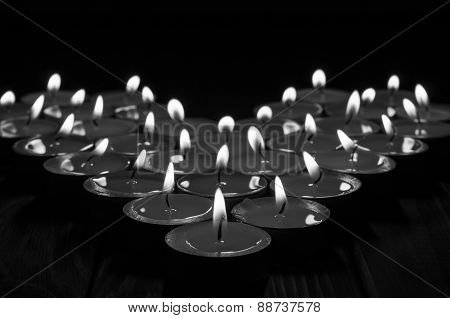 Black and white candles in the shape of heart on old wooden background