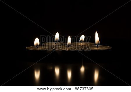 Five candles on a dark background reflected from the surface
