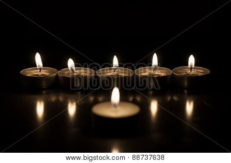 One candle and group of candles on old wooden background
