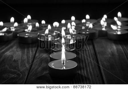 Candle and blurry candles on old wooden background