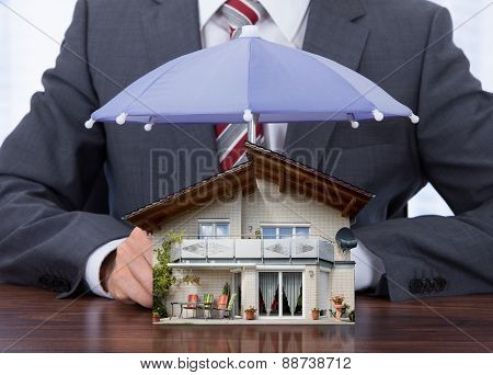 Businessman Sheltering House With Umbrella