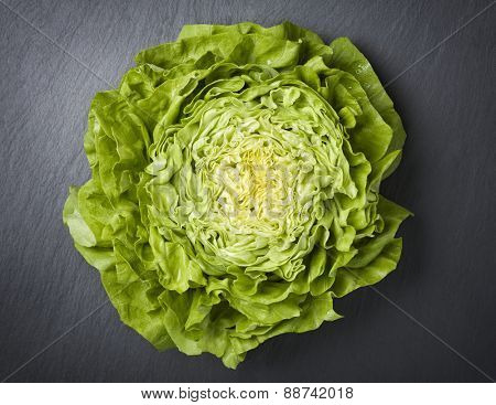 Healthy eating concept with sliced half head of lettuce isolated on a dark grey stone background.