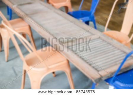 Blurry Defocused Image Of Orange And Blue Metal Chair With Old Wooden Door For Background