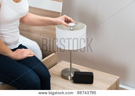 Woman Fixing Lamp At Home