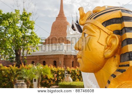Left Side Of Golden Pharaoh Statue With Pagoda Background