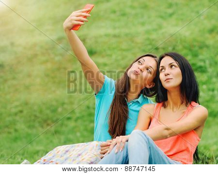 Two Women Friends Taking Pictures Of Themselves With Phone On Picnic At The Park