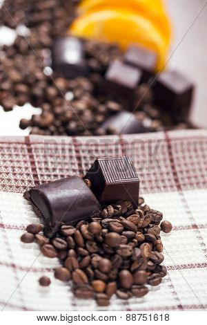 Chocolate, orange and coffee beans on wooden table