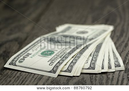 hundred dollar bills on wooden table