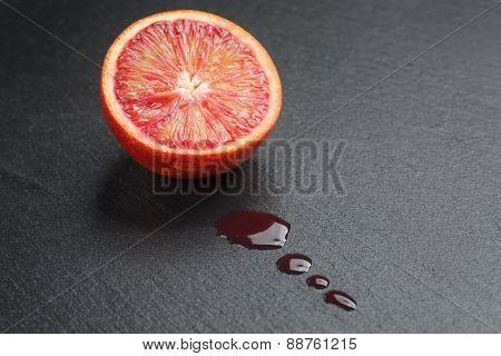 red sicilian orange sliced on slate board with juice drops