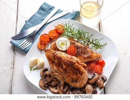 Baked Chicken Breast With Mushrooms And Carrots On Plate