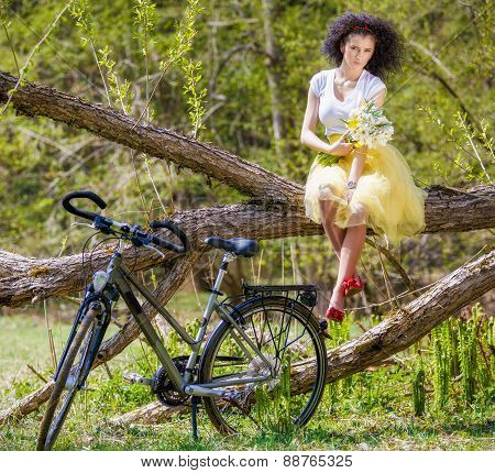 beautiful young woman with a bicycle in nature
