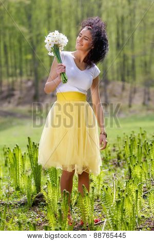 young woman with a bouquet of daffodils in nature