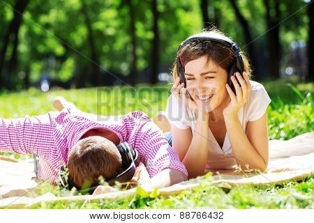 Loving young couple in summer park listening music