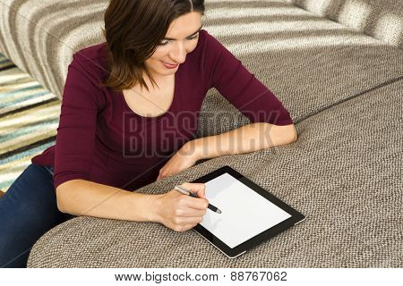 Gorgeous woman at home working with a tablet