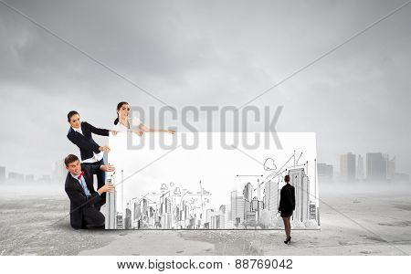 Small group of business people holding banner with construction project