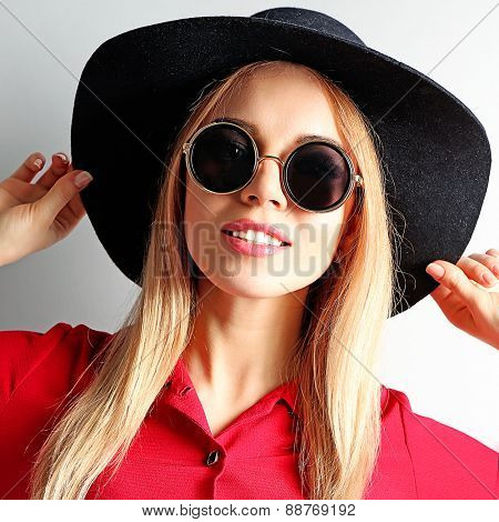 Portrait of young model in red dress, black hat and sunglasses on gray background