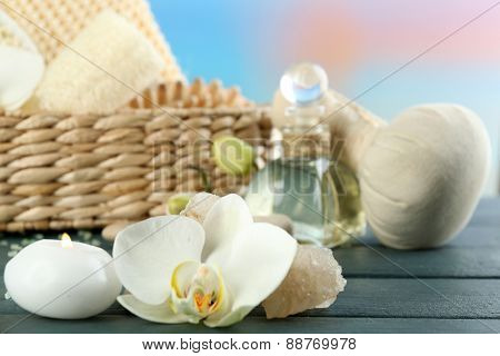 Still life with candle, pebbles and  spa treatment on wooden table, on bright background