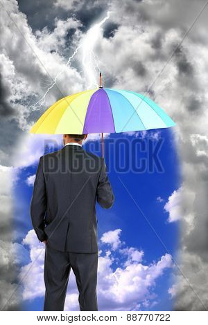 Business man standing in rain with umbrella