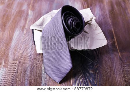 Male necktie in box on wooden background