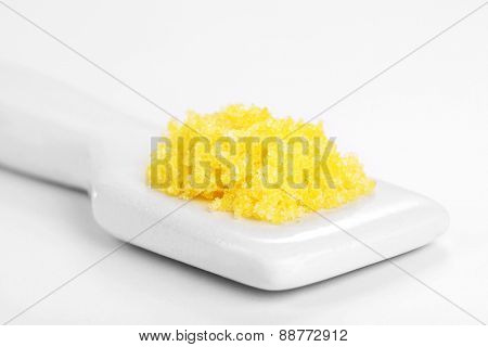 Laboratory spatula with granules isolated on white