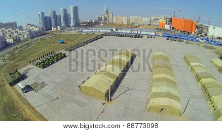 MOSCOW, RUSSIA - APRIL 20, 2014: Military base with tents and machines prepared for Victory Day Parade and construction site of trade center Aviapark at spring sunny day, aerial view