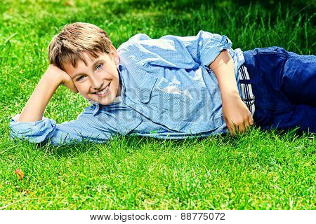 Cute boy lying on a grass at a park and smiles. Summer day. Holiday.