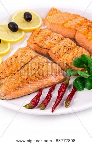 Salmon fillet on plate with lemon and peppers