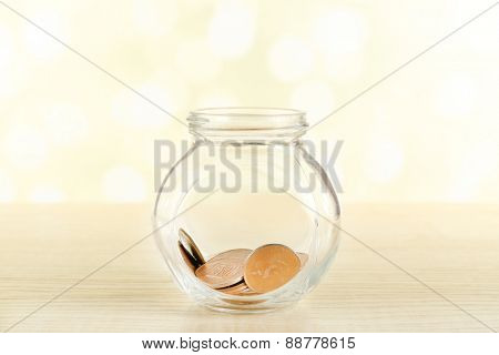 Gold coins in glass bottle on bright background
