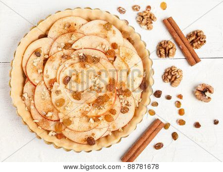 Homemade apple raw pie preparation. Tart with apples, raisins, nuts and cinnamon