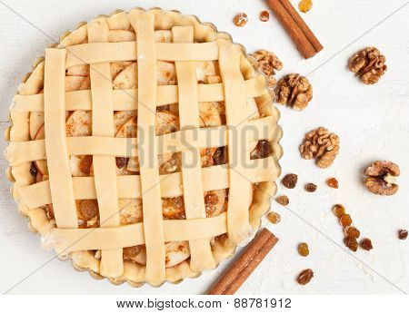 Homemade sweet pastry apple pie preparation. Raw tart with nuts, cinnamon and raisins