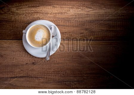 Cup Of Freshly Brewed Aromatic Cappuccino Standing On A Wooden Table