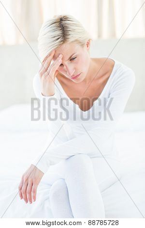 Worried blonde woman sitting on the bed in the bedroom