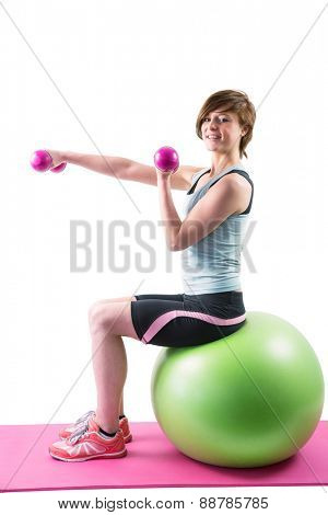 Pretty brunette looking at camera and exercising with dumbbells on fitness ball on white background