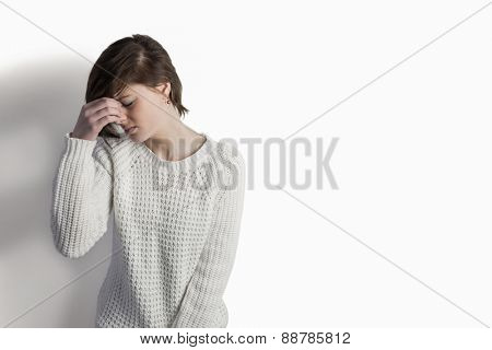 Sad pretty brunette leaning against wall on white background