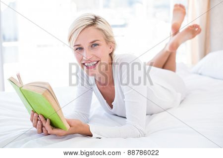 Smiling blonde woman lying on the bed and reading a book in her bedroom