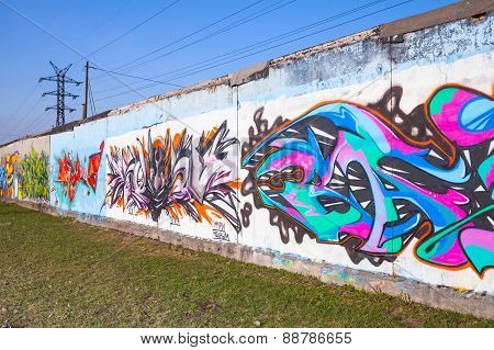 Colorful Graffiti With Chaotic Patterns Over Old Gray Concrete Garage Walls