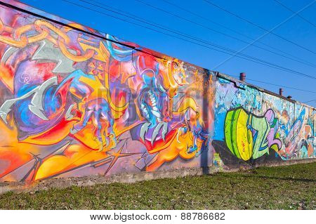 Colorful Graffiti With Dragon And Chaotic Patterns Over Old Gray Concrete Garage Wall