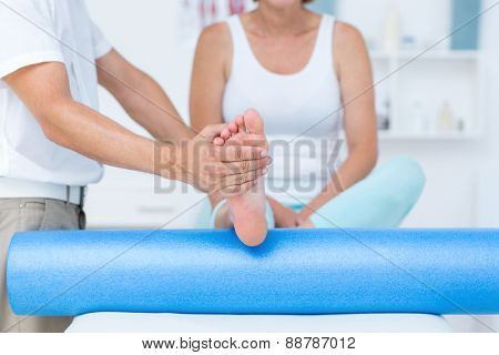 Doctor examining his patients leg in medical office