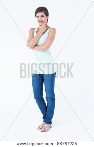Thoughtful woman smiling at camera on white background