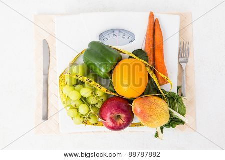 Weighing scales with fruits and vegetables on white background