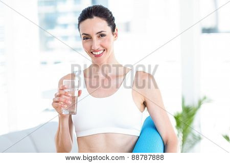 Smiling brunette holding exercise mat and glass of water in the living room