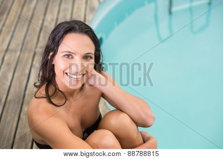 Beautiful woman in bikini relaxing by swimming pool