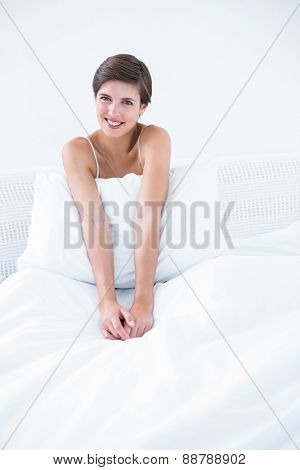 Happy brunette smiling at camera in her bed at home in the bedroom