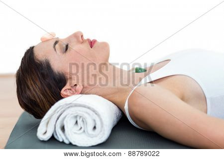 Relaxed brunette lying on mat with stones on white background