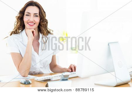 Smiling businesswoman working with her computer on white background