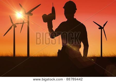 Carpenter holding cordless drill over white background against sunset