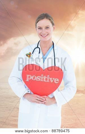 The word positive and doctor holding red heart card against sunrise over magical sea