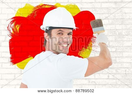 Portrait of happy man using paintbrush against white wall