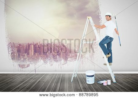 Happy man on ladder painting with roller against room with large window looking on city