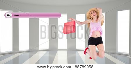 Pretty young blonde holding shopping bags against bright room with windows